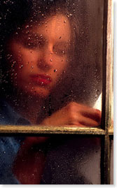 woman behind a rain covered window